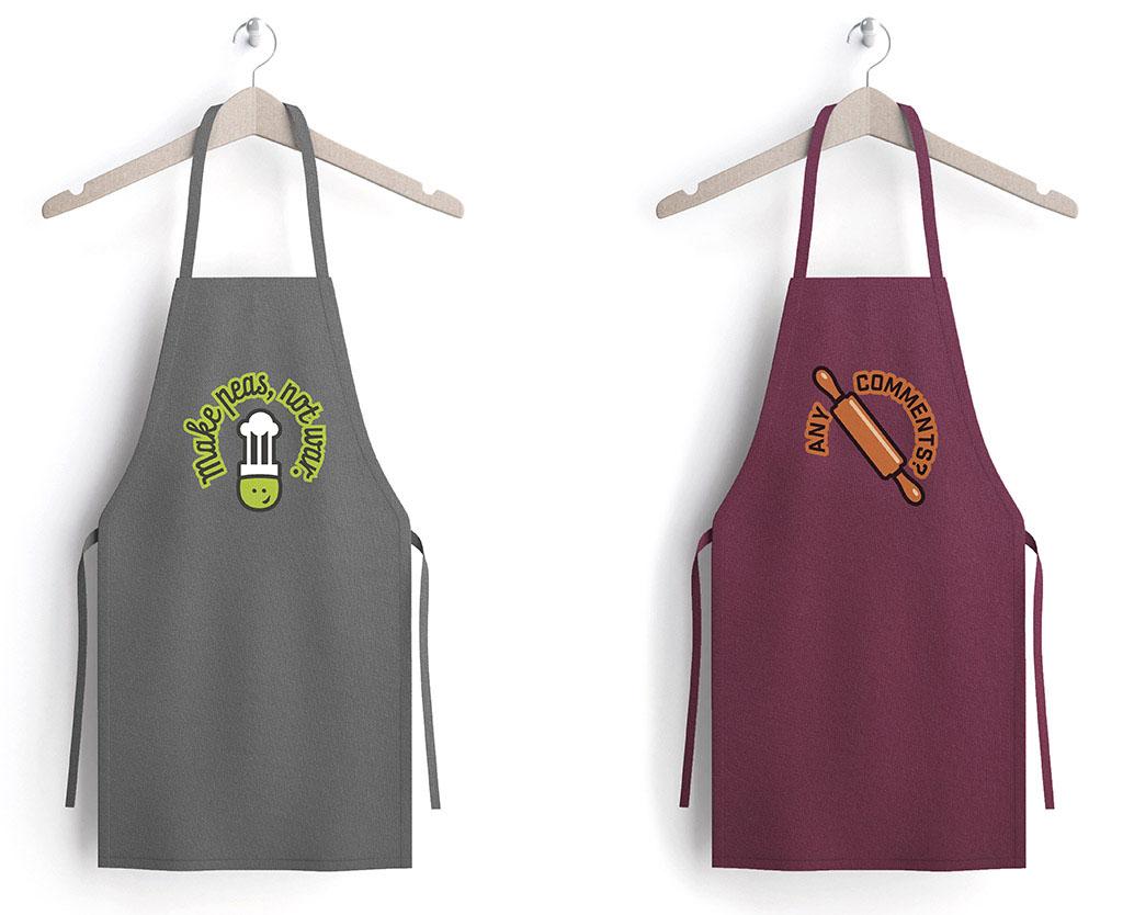 Zwei Kochschürzen mit lustigen Motiven an zwei Kleiderbügeln