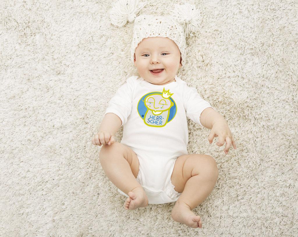 """Ein Baby trägt einen Strampler mit der Aufschrift: """"Herrscher"""""""