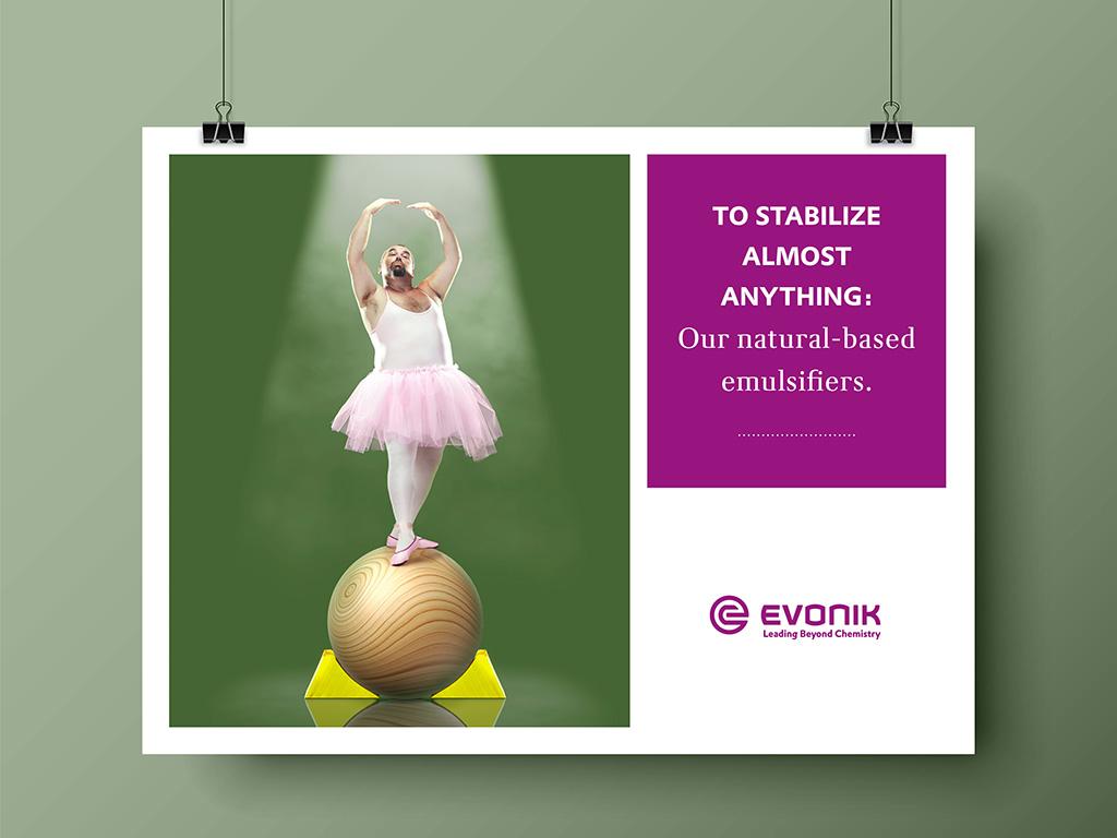 """Eine männliche Ballerina balanciert auf einem Ball, der von zwei Unterlegkeilen gehalten wird; Headline: """"To stabilize almost anything: Our natural-based emulsifiers."""""""